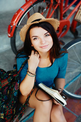 young girl posing in the street with bicycle and a notebook