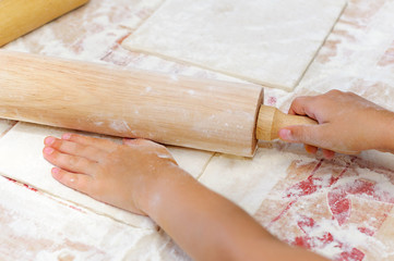 child unrolls dough with rolling pin