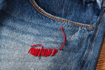 blue jean texture with a hole and threads showing