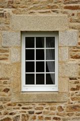 Modernes Kunststofffenster mit Rollladen in Natursteinfassade