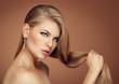 Cute model holding her long hair wearing brilliant earrings