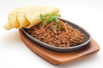 Fried minced lamb meat with loaf on a hot plate