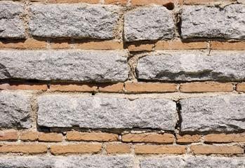 Old stone wall with bricks closeup