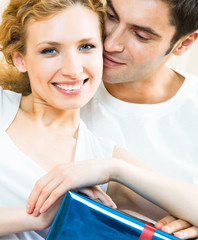 Cheerful amorous couple with gift, indoors