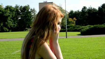 young attractive woman goes in park  - nature - woman telephone