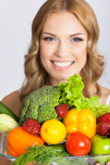 Young woman with vegetarian food, over gray