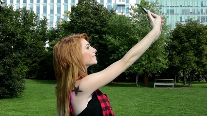 young attractive woman photographs herself (selfie) - nature