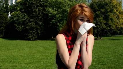 young attractive blowing her nose with handkerchief-park