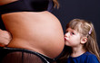 Child kissing belly of pregnant woman against black background