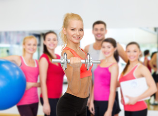 young sporty woman with heavy steel dumbbell