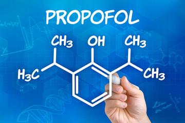Hand mit Stift zeichnet chemische Strukturformel von Propofol