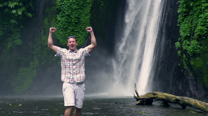 Happy man feeling free next to the waterfall, slow motion shot