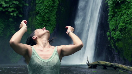 Happy woman feeling free next to waterfall, slow motion 240fps