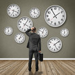 Man stands in front of a wall with clocks