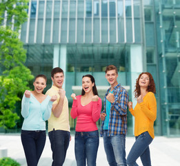 group of smiling teenagers showing triumph gesture