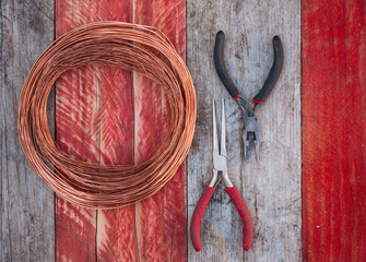 copper wire and pliers on grungy wood background