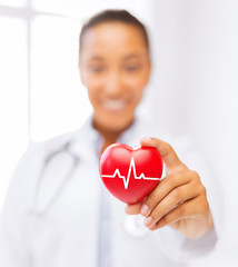 female doctor holding red heart with ecg line