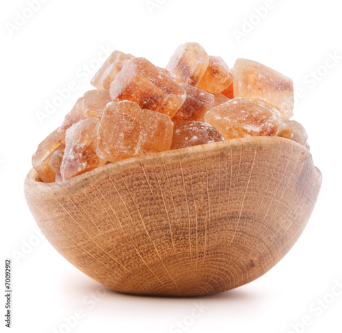 canvas print picture Brown cane caramelized lump sugar in wooden bowl isolated on whi