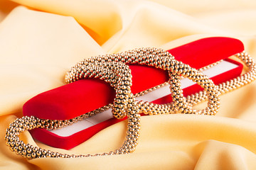 Modern golden necklace on the yellow silk