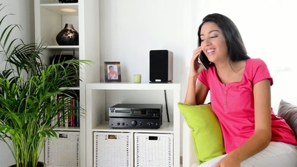 cheerful young woman making a phone call at home