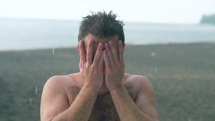 Sad man looking to the camera while raining, slow motion shot
