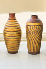 Two similar ornamented pots standing on the floor