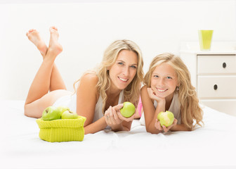 Beautiful mother and daughter together with apple