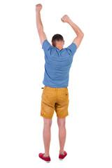Back view of  joyful man celebrating victory hands up.