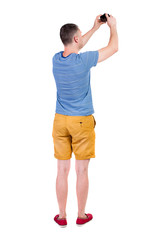 Back view of man photographing.  tourist in shorts.