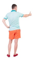 Back view of  man in shorts shows thumbs up.