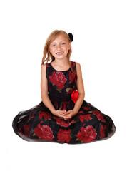 Smiling girl sitting on floor.