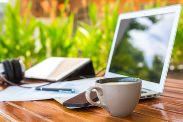 Laptop, tablet , smartphone and coffee cup with financial docume
