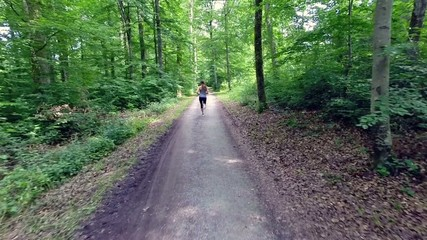 young woman jogging through forest
