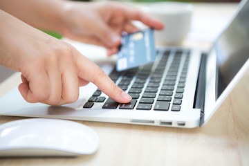 Hands holding a credit card and using laptop computer for online