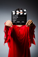 Man in red dress with movie clapboard