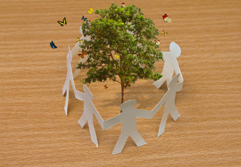 Paper cut of people standing in a circle around tree