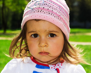 closeup portrait of Cute kid thinking at the park