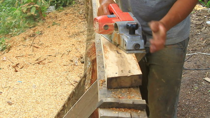 carpenter worker's power tool while planing a piece of wood