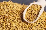 wooden scoop with fenugreek seeds