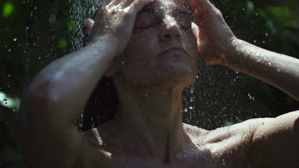 Woman having a shower in the garden, slow motion shot