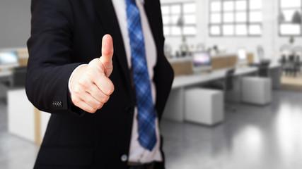 Geschäfsmann mit Daumen-Hoch-Geste vor Bürohintergrund