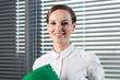 Smiling secretary holding green folder