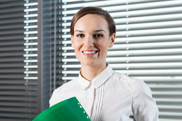 Smiling secretary holding green folder