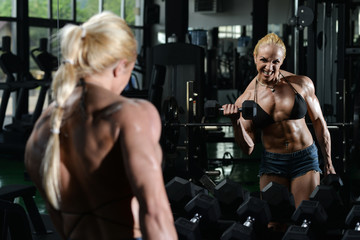 Woman Bodybuilder Exercising Biceps With Dumbbells