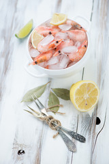 Bowl with raw iced shrimps, lime, lemon and bay leaves