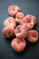 Donut peaches over black wooden surface, high angle view