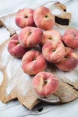 Chinese flat peaches over wooden background, studio shot
