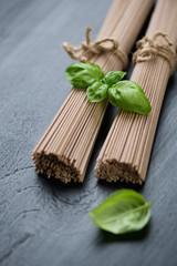 Close-up of raw soba noodles with green basil, studio shot