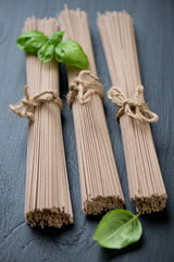 Buckwheat soba noodles with green basil, vertical shot