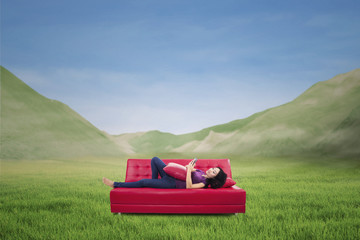 Attractive female lying on red sofa outdoor